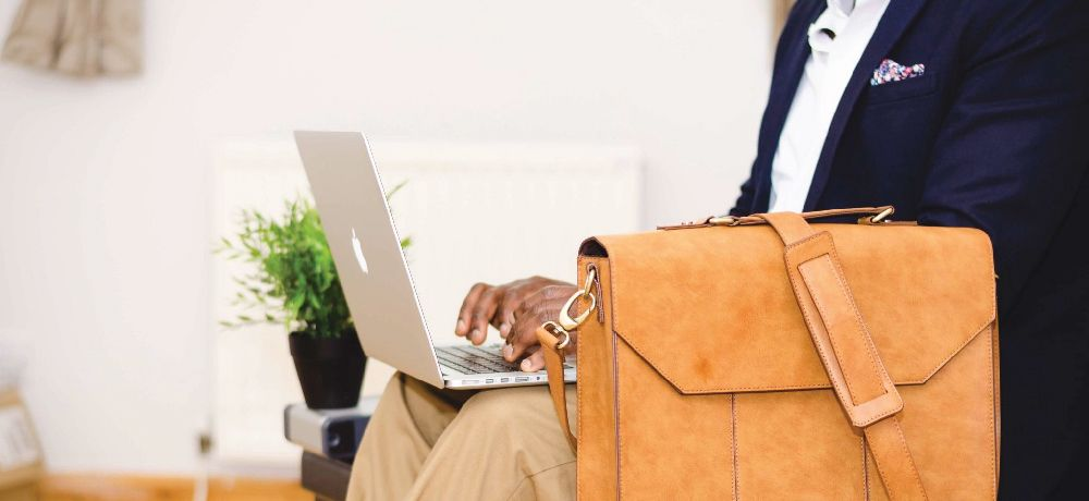 Man sitting at laptop with briefcase